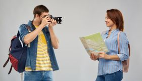 Happy couple of tourists with backpacks and camera. Travel, tourism and vacation concept - happy couple of tourists with backpacks, map and camera photographing royalty free stock image