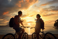 Happy couple tourists with bicycles watching sunset. Silhouette Stock Photos