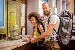 Happy couple of tourists buy tickets at terminal station counter. Happy couple of tourists buy tickets for their journey at terminal station ticket counter Royalty Free Stock Image