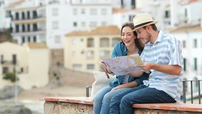 Happy couple of tourists checking map and contemplating views stock footage