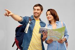 Happy couple of tourists with city guide and map. Travel, tourism and vacation concept - happy couple of tourists with city guide, map and backpacks over grey stock image