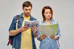 Happy couple of tourists with city guide and map. Travel, tourism and vacation concept - happy couple of tourists with city guide, map and backpacks over grey stock images