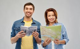 Happy couple of tourists with city guide and map. Travel, tourism and vacation concept - happy couple of tourists with city guide and map over grey background royalty free stock photography