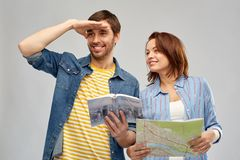 Happy couple of tourists with city guide and map. Travel, tourism and vacation concept - happy couple of tourists with city guide and map over grey background stock images