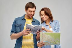 Happy couple of tourists with city guide and map. Travel, tourism and vacation concept - happy couple of tourists with city guide and map over grey background royalty free stock image