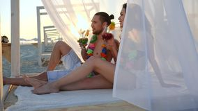 Happy couple of tourists drink cocktails and wearing flower hawaiian Lei, white cloth, bungalow, an exotic vacation stock footage
