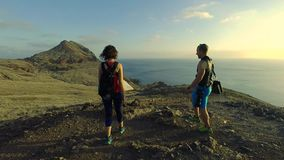 Happy couple of tourists is hiking on Madeira island. Exploring map, backside view. Full HD footage. They are seeking for adventures and special places stock video footage