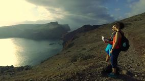 Happy couple of tourists is hiking on Madeira island. Exploring map, side view. Full HD footage. They are seeking for adventures and special places stock video footage