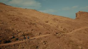 Happy couple of tourists is hiking on Madeira island. 4K footage. Side view from drone. Happy couple of tourists is hiking on Madeira island. They are going by stock footage