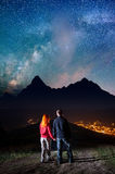 Happy couple tourists holding hands, standing on a hill and enjoying incredibly beautiful starry sky. Low light Royalty Free Stock Image