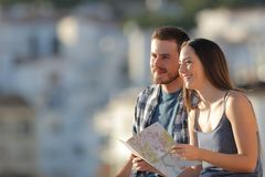 Happy couple of tourists holding map contemplating views. Happy couple of tourists holding paper map contemplating views in a town on vacation stock photos
