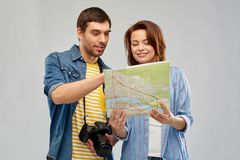 Happy couple of tourists with map and camera. Travel, tourism and vacation concept - happy couple of tourists with map and camera over grey background royalty free stock photography