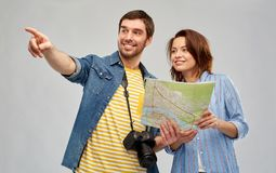 Happy couple of tourists with map and camera. Travel, tourism and vacation concept - happy couple of tourists with map and camera over grey background stock photography