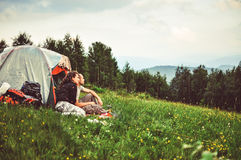 Happy couple of tourists rest in the mountains. stock photos