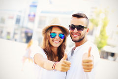 Happy couple of tourists showing ok in the city Royalty Free Stock Photo