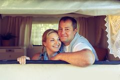 Happy couple of tourists sitting in a camper van.
