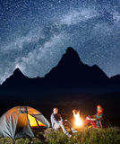 Happy couple tourists sitting near campfire and tent under incredibly beautiful starry sky at night. Long exposure Royalty Free Stock Photos