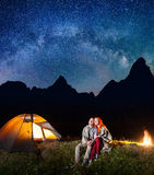 Happy couple tourists sitting together near campfire and shines camp at night under stars and looking to the starry sky. Happy couple tourists covered with a Stock Photography