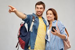 Happy couple of tourists with smartphone. Travel, tourism and vacation concept - happy couple of tourists with smartphone and backpacks over grey background royalty free stock photos