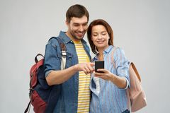 Happy couple of tourists with smartphone. Travel, tourism and vacation concept - happy couple of tourists with smartphone and backpacks over grey background stock photos
