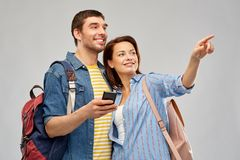 Happy couple of tourists with smartphone. Travel, tourism and vacation concept - happy couple of tourists with smartphone and backpacks over grey background royalty free stock image