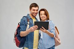 Happy couple of tourists with tablet computer. Travel, tourism and vacation concept - happy couple of tourists with tablet computer and backpacks over grey royalty free stock images