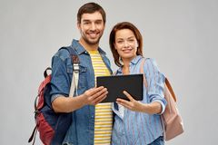 Happy couple of tourists with tablet computer. Travel, tourism and vacation concept - happy couple of tourists with tablet computer and backpacks over grey stock images