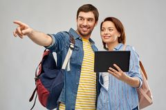Happy couple of tourists with tablet computer. Travel, tourism and vacation concept - happy couple of tourists with tablet computer and backpacks over grey stock photo