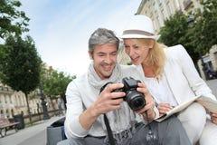 Happy couple of tourists taking photos Stock Photos