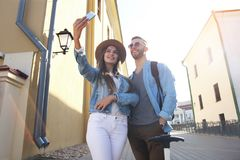 Happy couple of tourists taking selfie in old city. Stock Photos