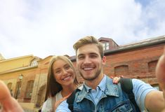 Happy couple of tourists taking selfie in old city. Royalty Free Stock Photo