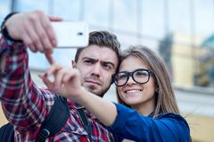 Happy couple of tourists taking selfie in showplace of city. Man and woman making photo on city background.  stock photos