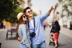 Happy young couple of tourists on vacations searching a street in a map and pointing away Royalty Free Stock Photography