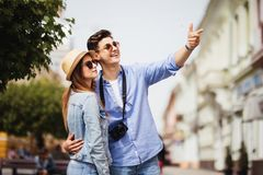 Happy young couple of tourists on vacations searching a street in a map and pointing away Stock Images