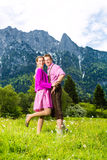 Happy couple in Alpine meadow royalty free stock photo