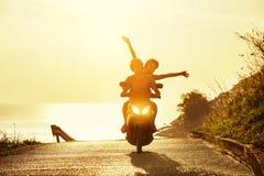 Happy couple travel motorcycle sea road. Happy couple traveling on motorcycle on sea coastal road. Travel concept Stock Photo