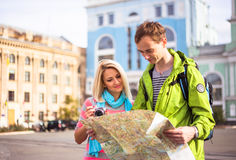 Happy couple on travel vacation holidays. Young beautiful women and men looking to map Stock Images