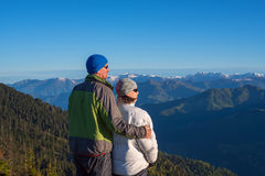 Happy couple of travelers is admiring the dawn in the mountains royalty free stock photo