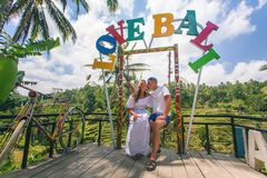 Happy couple traveling at Bali, rice terraces of Tegalalang, Ubud. Text of Love Bali above their heads. Honeymoon summer travel at Indonesia. Happy people stock photography