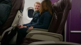 Happy couple traveling by plane on vacation, holding hands, enjoying flight. Stock footage stock video footage