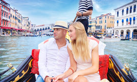 Happy couple traveling to Italy. Young happy couple swimming on the gondola on Grand Canal in Venice, with pleasure spending honeymoon in Europe stock images