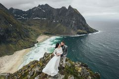 Wedding couple travelers on a hill in Norway, Kvalvika. Beautiful view of the beach, Lofoten, Norway. stock photography