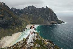 Wedding couple travelers on a hill in Norway, Kvalvika. Beautiful view of the beach, Lofoten, Norway. stock image