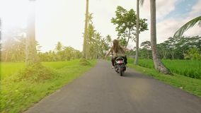Couple riding their scooter through forest. life style idea concept. Young beautiful couple rides the jungle on a stock footage