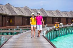 Happy couple on tropical beach jetty going to the. Couple on tropical beach jetty going to the beach at Maldives Royalty Free Stock Images