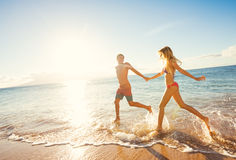 Happy Couple on Tropical Beach at Sunset Stock Photo