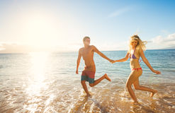 Happy Couple on Tropical Beach at Sunset Royalty Free Stock Photo