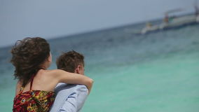 Happy couple on tropical beach. Young girl on her back at the man, the man turns with the girl.Behind the sea and boats.Love and the romantic on the tropical stock video