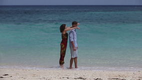 Happy couple on tropical beach. A young man stands on the beach, the girl jumps behind his back.Love and the romantic on the tropical island.Travel holidays stock footage