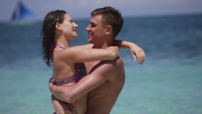 Happy couple on tropical beach. Young pair stand having embraced on a tropical beach and look at each other, the girl touches hair to the man. Behind them the stock footage